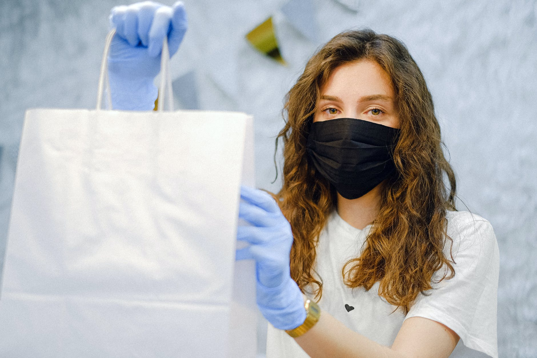 woman with face mask and latex gloves holding a shopping bag